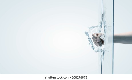 Close up of male fist breaking glass with punch