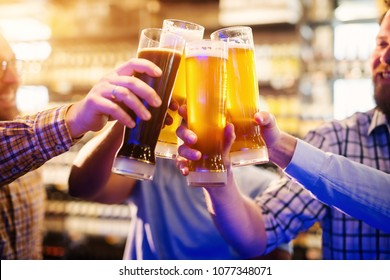 Close up of male friends hands clinking with draft beer and celebrating the end of the week.