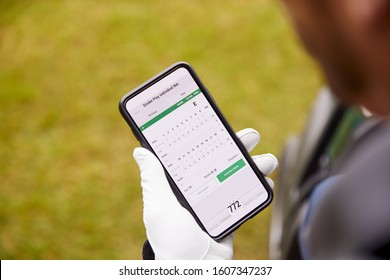 Close Up Of Male Golfer In Buggy Checking Score On Mobile Phone App