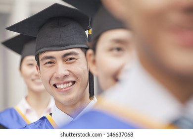 Close Up of Male Graduate Student Standing in a Row of Graduates