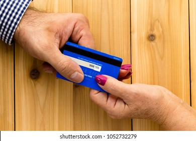 Close up of male hand giving credit card to woman against wooden table