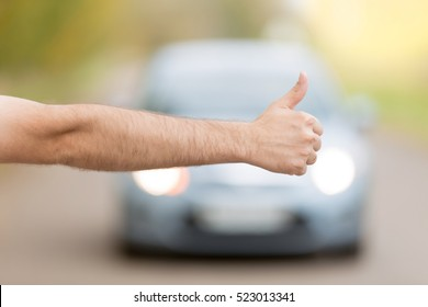 Close up of male hand hitchhiking, asking a coming car for a ride on summer street