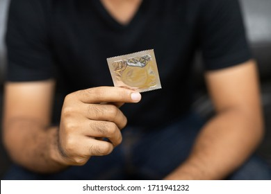 Close up Male hand holding Condom. Safe sex concept.