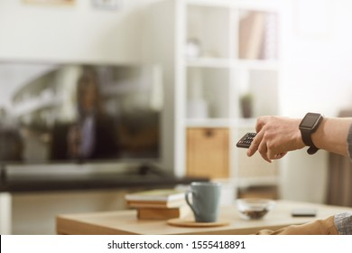 Close up of male hand holding remote control, concept of modern young man watching TV at home, copy space