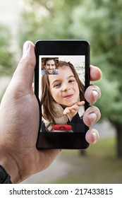 Close Up Of A Male Hand Holding A Smart Phone During A Video Call With His Daughter