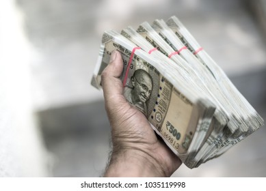Close up of a male hand holding stack of Indian Rupee notes. Cash transaction with new Indian currency notes.
