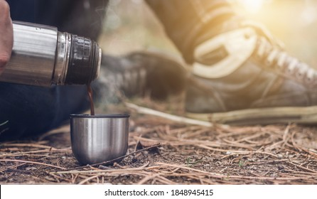 Close up of male hand holding a thermo and pouring a hot beverage in the small mug on the forest floor. Man sits on the ground and pours a tea or coffee from a metal thermos bottle into a cup.