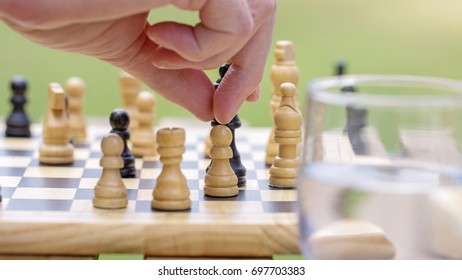 Close up of male hand making a move on a chess board