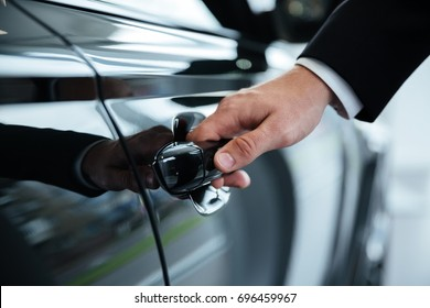 Close up of a male hand opening a car door at the dealership