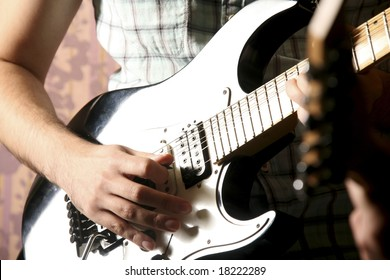 close up male hand playing a guitar