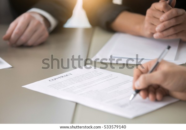 Close up of male hand putting signature, running own small business, have a contract in place to protect it, basics of writing contract, one sentence in a contract can cost a business, handwriting