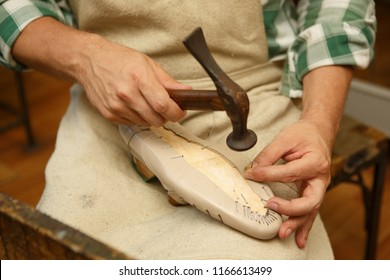 Close up of male hand shoemaker sitting in workshop working with hammer at workshop. Man wearing in apron, with one hand holding nail, second hand hammer, preparing to slaughter nail in wooden shape.