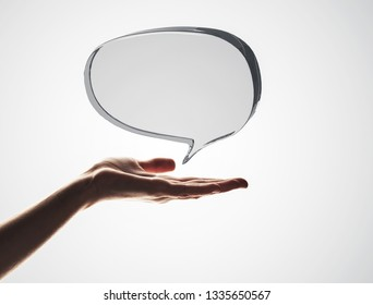 Close of male hand showing shiny glass speech bubble. 3d rendering