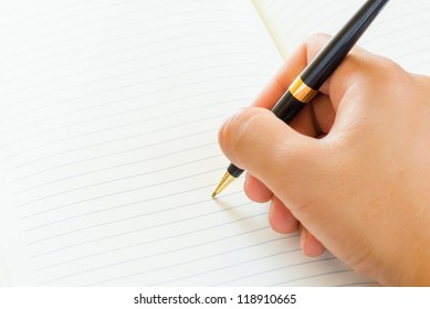Close up of male hand signing a contract on blank white paper.