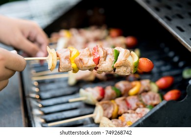 Close up male hand touches barbeque on skewers in grill stove.