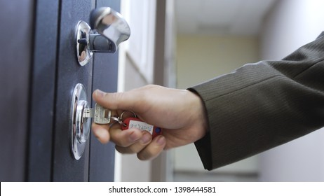 Close up of male hand unlocks a house's door with the key