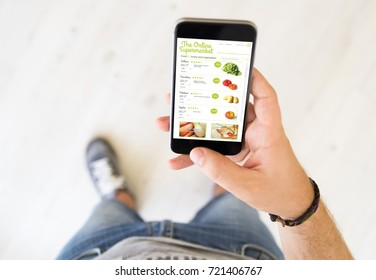close up of male hand using online supermarket app smart phone