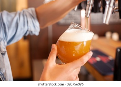 Close up of male hands of barman. He is holding a glass and taping beer into it carefully. The man is standing in bar
