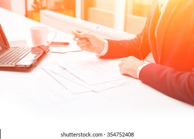 Close up male hands businessman. Closeup table and document. Businessman working at sunset with documents. Business man using laptop on table in with a cup of coffee. Background image.