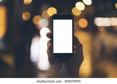 Close up of male hands hoding modern smart phone with blank screen for your text message or content, man's hand using cellphone at night city, bokeh light