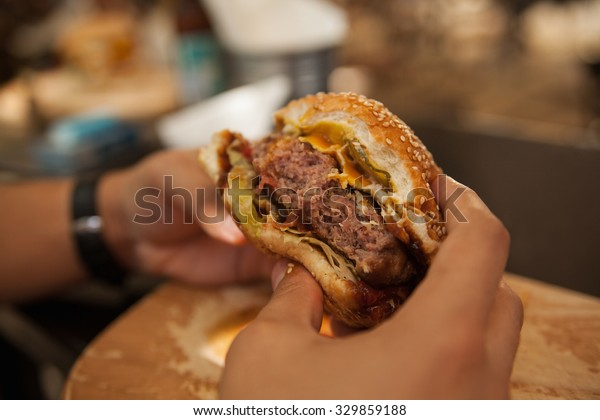Close Up Of Male Hands Holding Delicious Burger