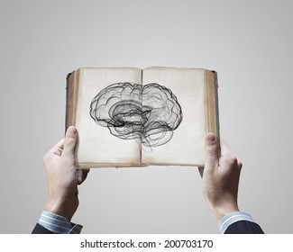 Close up of male hands holding opened book with brain picture