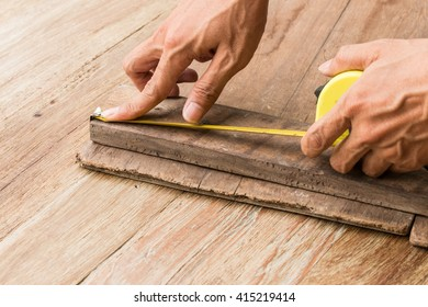 close up of male hands measuring wood floor