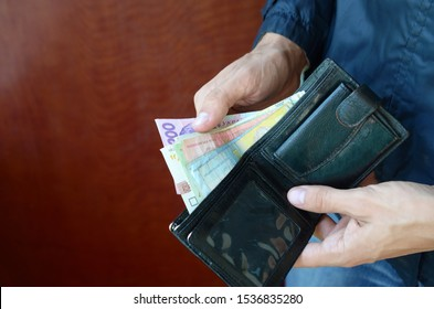 Close up male hands opened the wallet or purse with ukrainian money currency hryvnia