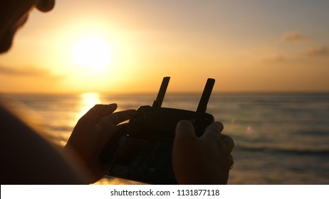 Close up of male hands operating a drone with remote control. Quadro copter drone flying over sunset ocean