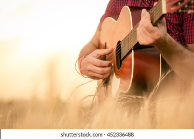Close up of male hands playing acoustic guitar on the wheat field at the sunset. Retro, music, lifestyle concepts.