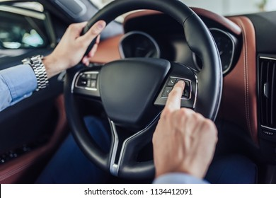 close up of male hands pushing button on the steering wheel in the car