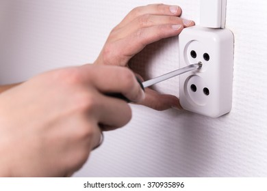 close up of male hands with screwdriver installing electrical socket on wall