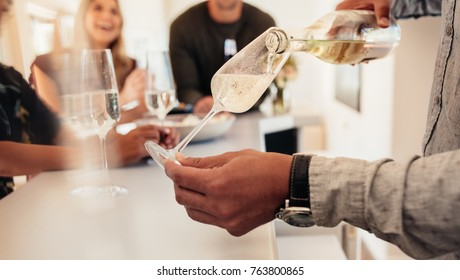 Close up of male hands serving champagne to guest standing in background. Man serving drinks to friends at new house.