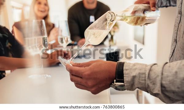 Nahaufnahme männlicher Hände, die Champagner servieren, um Gäste im Hintergrund zu sehen. Mann serviert Getränke an Freunde in einem neuen Haus.