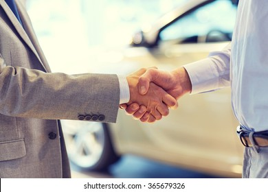 close up of male handshake in auto show or salon