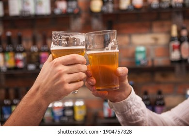 Close up of male hans with beer glasses clinking