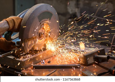 Close up of male industrial worker hand, cutting metal frame with compound miter saw with sharp circular blade, sparks flying around during working at workshop. Dangerous and hard work concept.