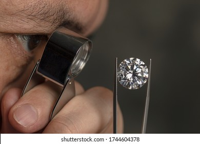 Close up male jeweller. Jeweller looking diamond though loupe. Cut and polished diamond. Big size diamond. Brilliant, magnifier, tweezers. Diamond expert.