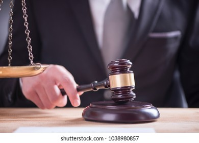 Close up of Male lawyer or judge hand's striking the gavel on sounding block. Law and justice concept.