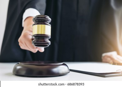 Close up of Male lawyer or judge hand's striking the gavel on sounding block, working with Law books, report the case on table in modern office, Law and justice concept.