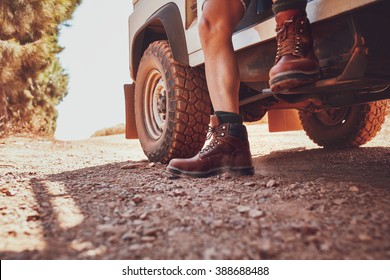 Close up of male leg with leather boot stepping out of a off road vehicle. Car parked on the dirt road in countryside.