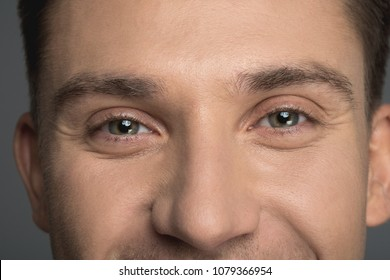 Close up of male light eyes staring at camera. Man is smiling