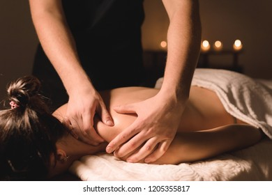 Close up Male manual worker doing spa massage to a young girl in a dark room