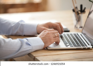 Close up of male married office worker using laptop browsing internet, businessman working at computer surfing web or reading news online, busy ceo or boss typing on keyboard checking email