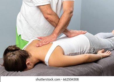 Close up of male osteopath doing manipulative physical treatment on female spine.
