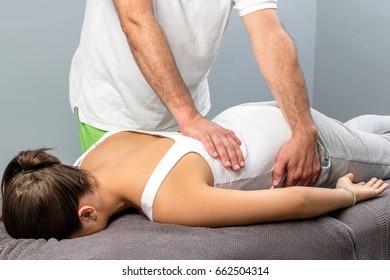 Close up of male osteopath doing manipulative massage on female lower back.