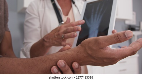 Close up of male patient hand and wrist with doctor explaining x ray on tablet