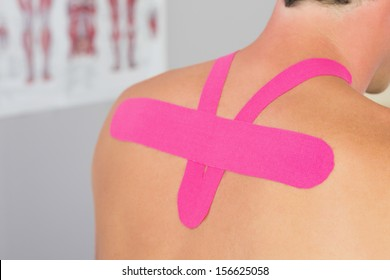 Close up of male patients back with applied pink kinesio tape in bright office
