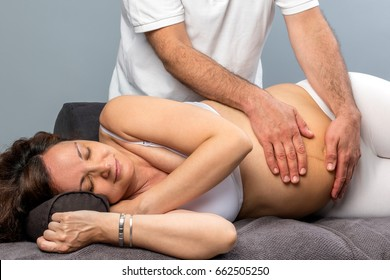 Close up of male physiotherapist massaging tummy on pregnant woman.