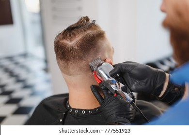 Close up of male professional hairdresser serving client by clipper. Ginger handsome stylish young man with big beard and short hair getting trendy haircut in black cape. Light white barber shop room